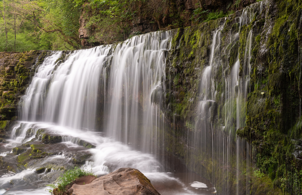 A long exposure photograph of Sgwd Isaf Clun-gwyn waterfall, four falls walk, waterfall country, Brecon beacons